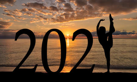 New Year 2021 sunrise by the beach with silhouette of woman in dance pose. Banque d'images