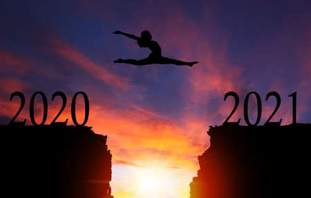 2021 New Year concept with silhouette of courageous girl jumping over cliff with dramatic sunset or sunrise background and copy space. Concept of going from Year 2020 to 2021. Banque d'images
