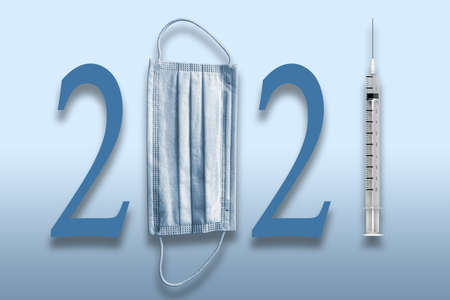 Happy New Year 2021 with protective surgical face mask and Covid-19 vaccine in a syringe needle. Concept of hope in the new year isolated on blue background.