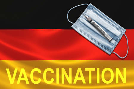COVID-19 vaccination in Germany concept with face mask and syringe needle vaccine on German Flag. Banque d'images