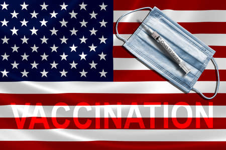 COVID-19 vaccination in the United States concept with face mask and syringe needle vaccine on U.S. Flag. Banque d'images