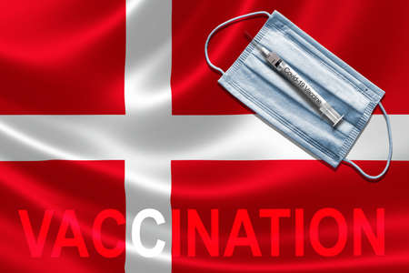 COVID-19 vaccination in Denmark concept with face mask and syringe needle vaccine on Danish Flag.