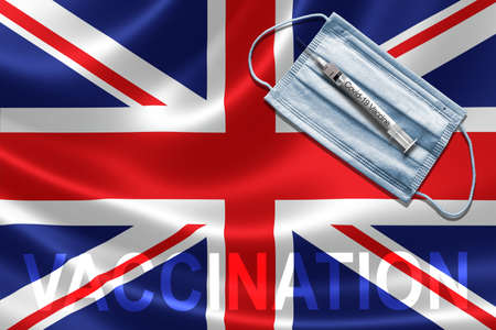COVID-19 vaccination in UK concept with face mask and syringe needle vaccine on British Flag.