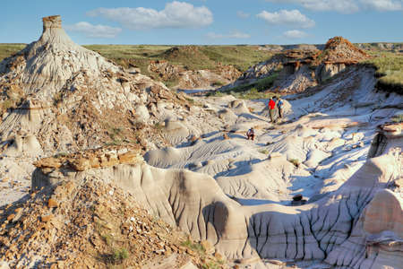 Unidentifiable tourists explore Dinosaur Provincial Park in Alberta, Canada, a Site noted for its striking badland topography and abundance of dinosaur fossils, one of the richest fossil locales in the world.