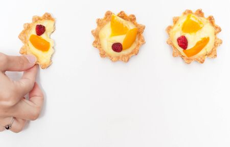 Berry, orange and apricot delicious cream tart. One of the tarts is torn apart by a hand. Фото со стока