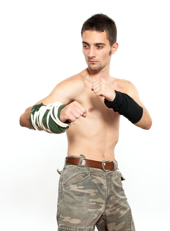 Powerful and aggressive young fighter ready for combat photo