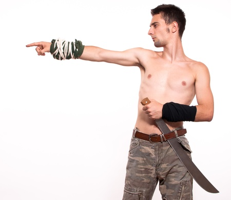 Powerful and aggressive young fighter holding a machete and pointing with finger