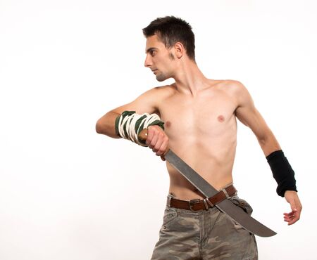 Powerful and aggressive young fighter holding a machete photo