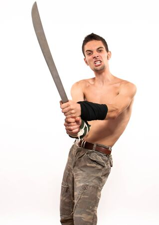Powerful and aggressive young fighter holding a machete