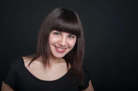 Portrait of lovely teenage girl on a dark background Фото со стока