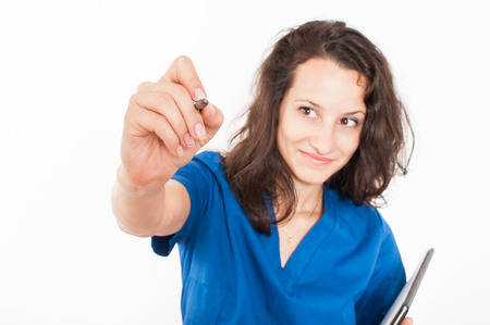 Young female doctor in blue coat writing Stock Photo