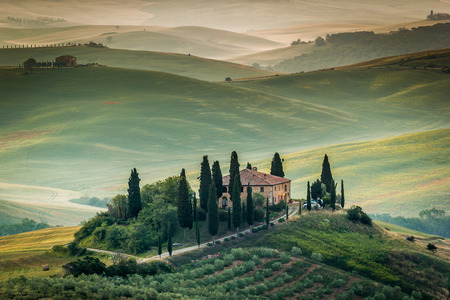 Val d'Orcia, Tuscany, Italy. A lonely farmhouse with cypress and olive trees, rolling hills. Stock fotó