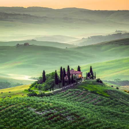 pienza: Val dOrcia, Tuscany, Italy. A lonely farmhouse with cypress and olive trees, rolling hills.