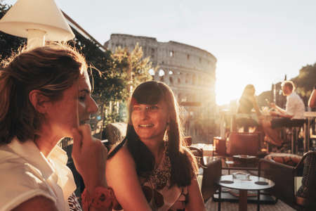 Two smiling women at sunset in Rome, Italy. Happy Hour