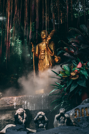 Statue at the Golden Mountain in Bangkok. 3 Monkeys in the foreground and in the back golden Statue between fog and the garden