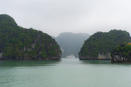 Halong Bay in mystical clouds. Mystical atmoshpere in the world famous halong bay. the limestone green rocks and the emerald green water gave a great contrast to the cloudy scene.