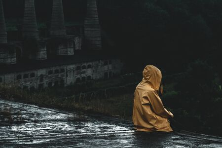Unrecognizable woman wearing a slicker and sits on the roof edge of an old abandoned factory building in a rainy mood atmosphere