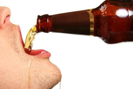bier wordt gegoten in de mond uit de fles Stockfoto
