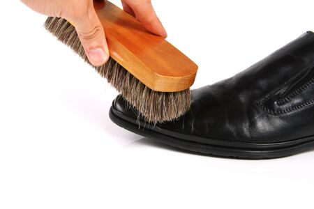 smooth wood: hand with brush cleaning shoe