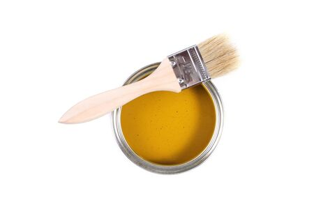 yellow paint can with brush isolated on a white background photo