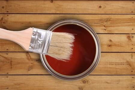 Red paint can with brush on wooden floor photo