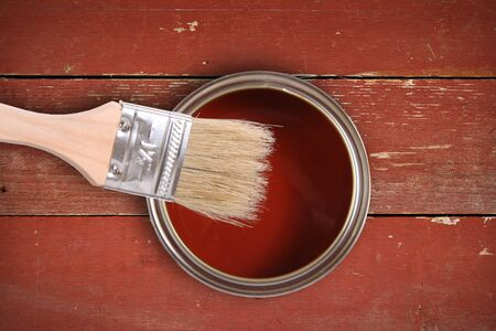 Red paint can with brush on wooden plank background photo