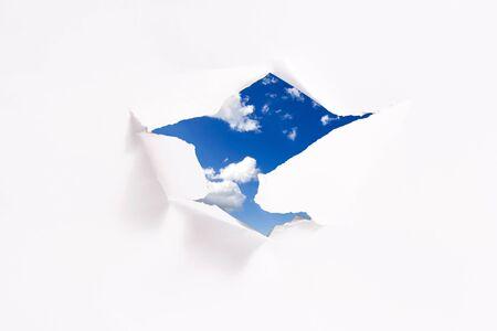 Concepto de la libertad: cielo azul detrás de agujero de papel