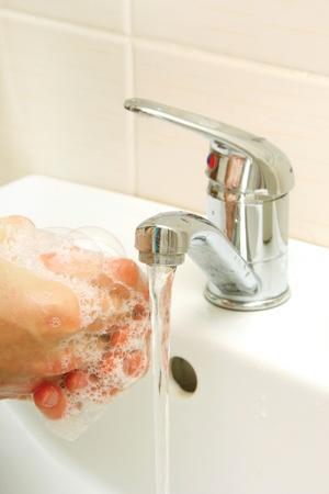 jabon liquido: Las manos cubiertas de jabón que se lava en el fregadero