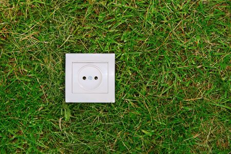 green energy concept: electric outlet on a grass photo