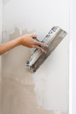 putty: work aligns - hand with putty knife Stock Photo
