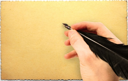 Hand writing with quill on old grungy postcard photo