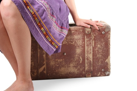 Woman sitting on old suitcase photo