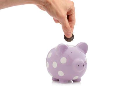 fondos violeta: Mano de insertar moneda en la hucha