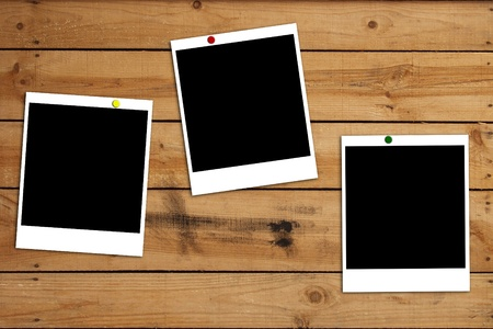 Blank photo frames on wooden plank background photo