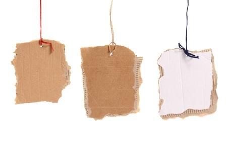 bribe: Trois balises carton suspendus sur fond blanc Banque d'images