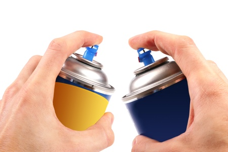two graffiti color spray cans in hands photo