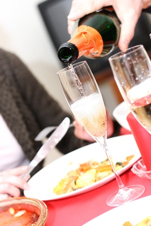 Glasses of champagne and candles: pouring champagne into a glass Kho ảnh