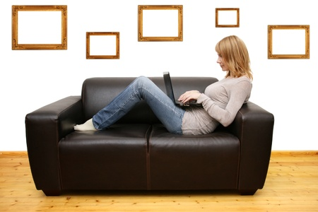 young woman lying on a sofa and using a laptop photo