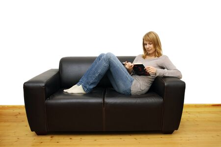 brown leather sofa: woman lying on a sofa and reading a book