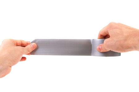 sticky hands: roll of duct tape in hands on white background