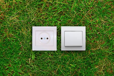 green energy concept: electric outlet and light switch on a grass photo
