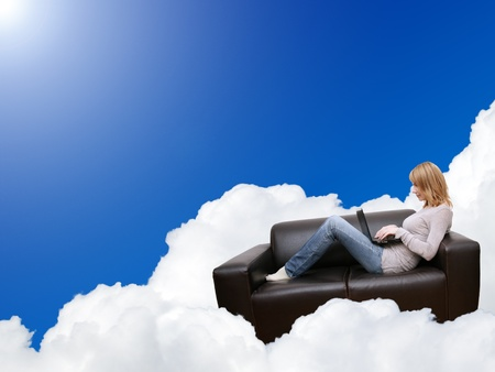 woman relaxing with laptop in couch on the cloud photo