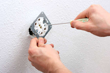 closeup of electrician hands installing wall socket photo