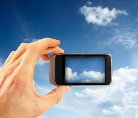 hand taking sky photo with smart phone  photo