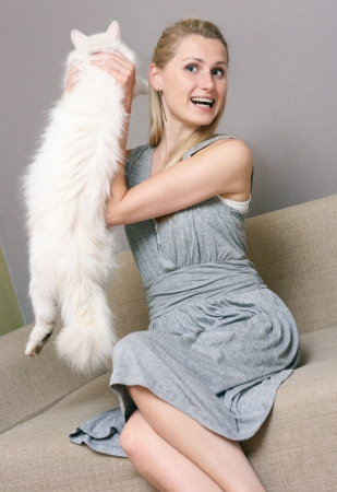 happy woman holding cat while sitting in couch photo