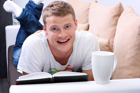 smiling young man reading a book and relaxing on sofa photo