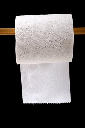 papel higienico: Rollo de papel higiénico colgando sobre fondo negro Foto de archivo