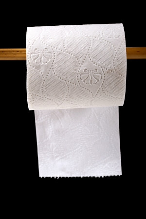 soft tissue: toilet paper roll hanging on black background