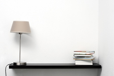 bookshelf on the wall with lamp and books photo