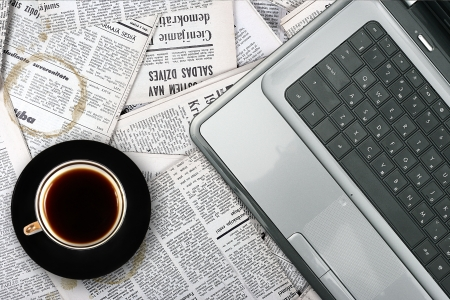 reading news: workplace with laptop and coffee cup on newspaper background Stock Photo